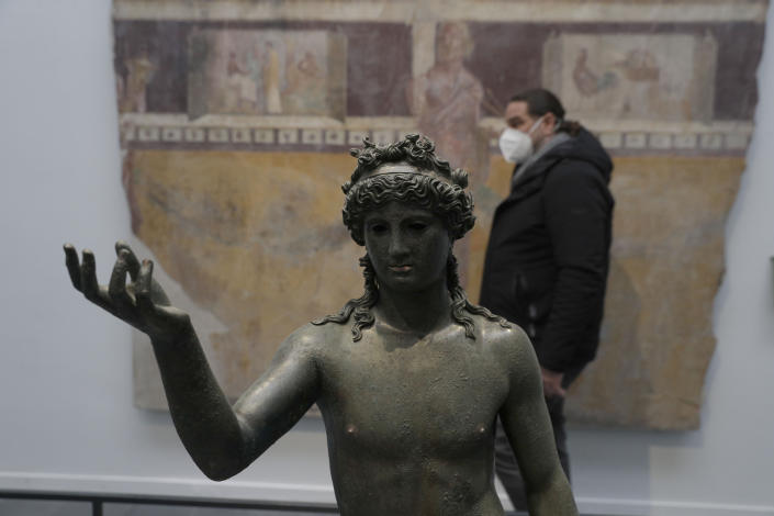 A man walks past the statue of Ephebos inside the museum Antiquarium in Pompeii, southern Italy, Monday, Jan. 25, 2021.Decades after suffering bombing and earthquake damage, Pompeii's museum is back in business, showing off exquisite finds from excavations of the ancient Roman city. Officials of the archaeological park of the ruins of the city destroyed in 79 A.D. by the eruption of Mount Vesuvius inaugurated the museum on Monday. (AP Photo/Gregorio Borgia)