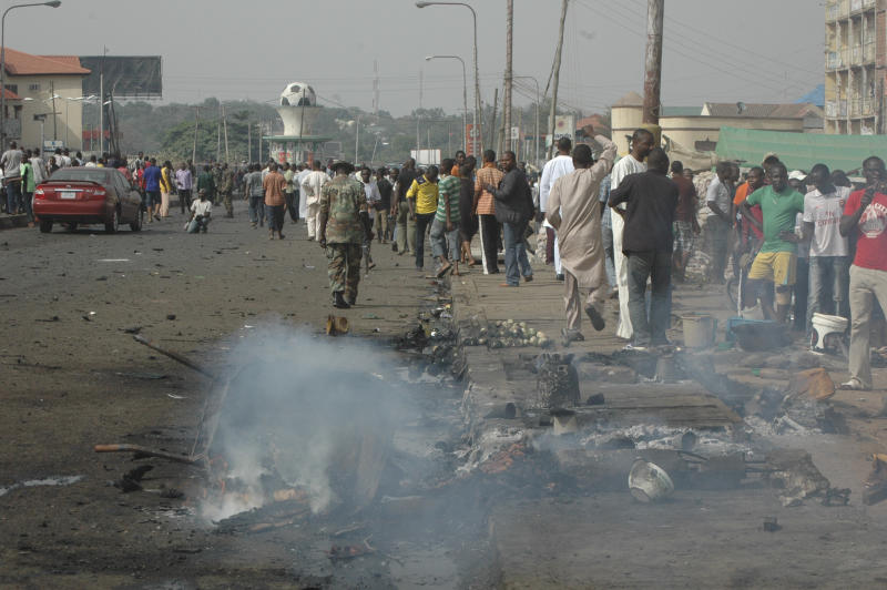People gather at the site of a bomb explosion at a road in Kaduna, Nigeria on Sunday, April 8, 2012. An explosion struck Sunday in Kaduna central Nigeria  that has seen hundreds killed in religious and ethnic violence in recent years, causing unknown injuries as diplomats had warned of possible terrorist attacks over the Easter holiday, police said.(AP Photos/Emma Kayode)