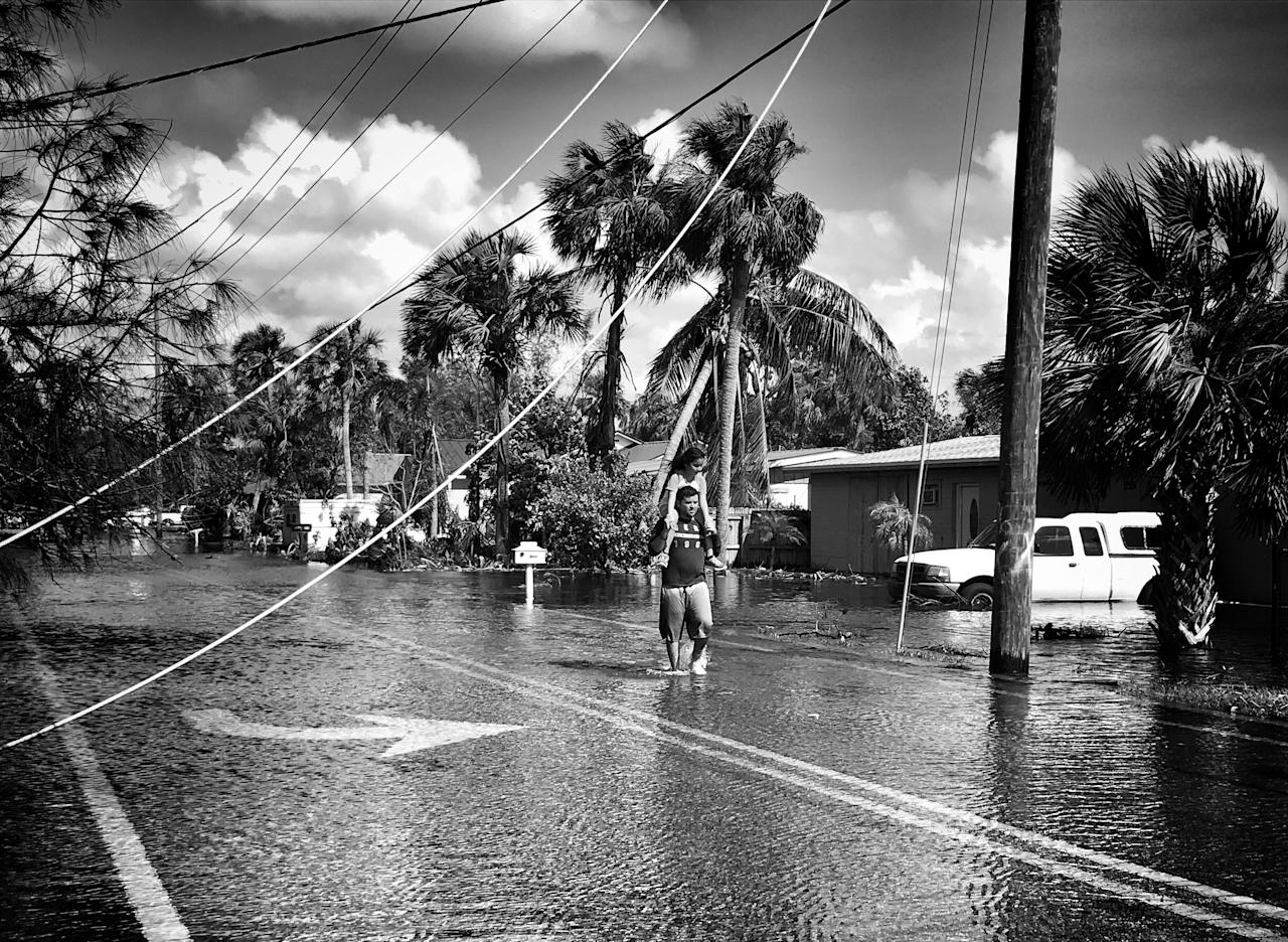 <p>A man carries a young girl on his shoulders in a flooded neighborhood in Bonita Springs, Fla. (Photo: Holly Bailey/Yahoo News) </p>
