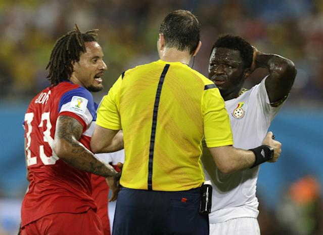 Referee Jonas Eriksson, centre, from Sweden speaks to United States' Jermaine Jones, left, and Ghana's Sulley Muntari during the group G World Cup soccer match between Ghana and the United States at the Arena das Dunas in Natal, Brazil, Monday, June 16, 2014. (AP Photo/Ricardo Mazalan)