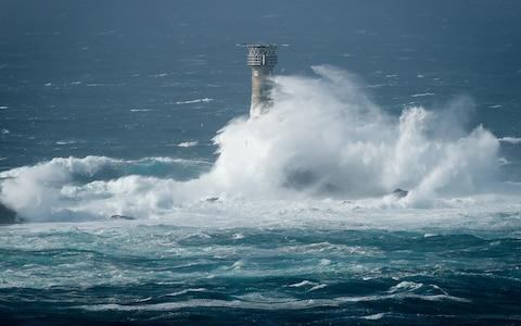 Waves break on Longships lighthouse off the coast of Lands End, Cornwall, - Credit: Ben Birchall/PA
