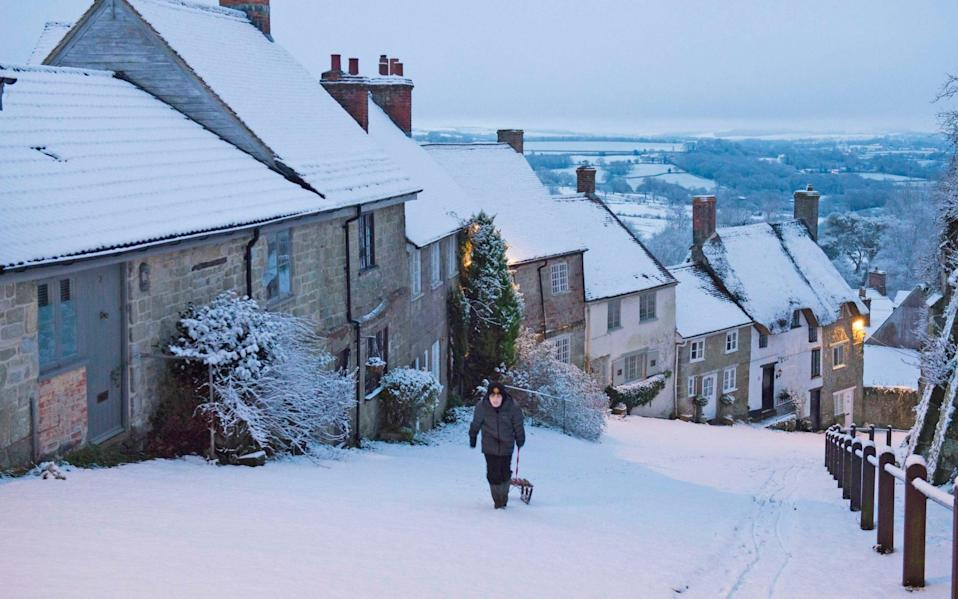 Kieron Taylor pulls his sled up the snow covered Gold Hill at Shaftesbury in Dorset at dawn - Graham Hunt/BNPS