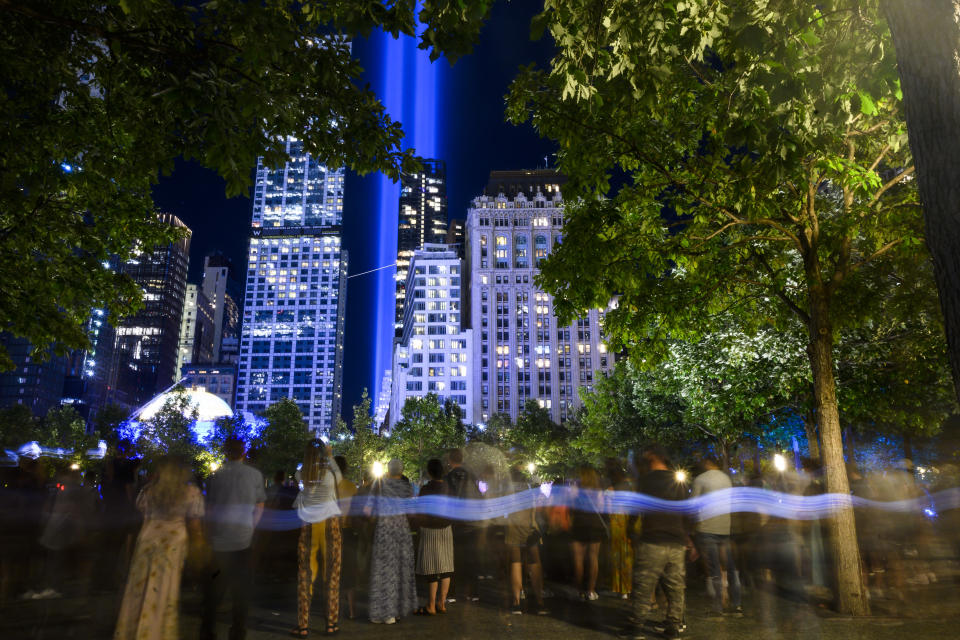 """A crowds looks at the annual """"Tribute in Light"""" illuminated on the 20th anniversary of the Sept. 11 attacks on Saturday, Sept. 11, 2021, in New York. (AP Photo/Brittainy Newman)"""