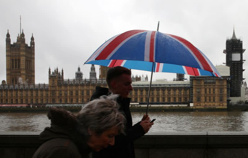 FILE PHOTO:  People walk over Westminster Bridge on a rainy day with the Houses of Parliament in the background in London