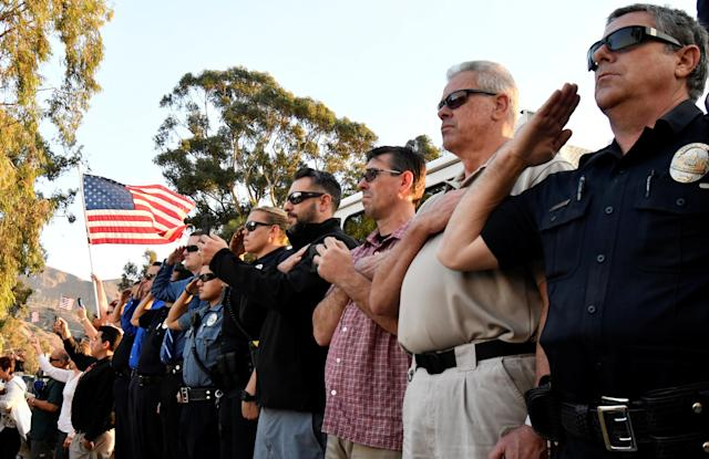 <p>Emergency personnel and residents salute as a procession of firefighting vehicles passes through Santa Paula, while carrying the body of a fellow firefighter who was killed today battling the Thomas wildfire near Fillmore, Calif., Dec. 14, 2017. (Photo: Gene Blevins/Reuters) </p>