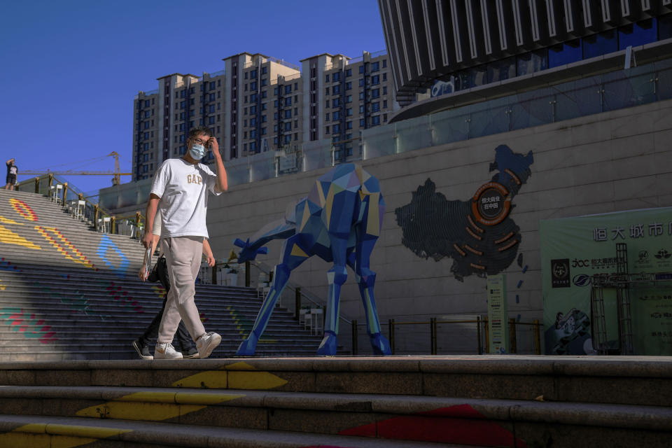 A man wearing a face mask to help protect himself from the coronavirus walks by a map showing the Evergrande development projects in China, at an Evergrande city plaza in Beijing, Tuesday, Sept. 21, 2021. Global investors are watching nervously as the Evergrande Group, one of China's biggest real estate developers, struggles to avoid defaulting on tens of billions of dollars of debt, fueling fears of possible wider shock waves for the Chinese financial system. (AP Photo/Andy Wong)