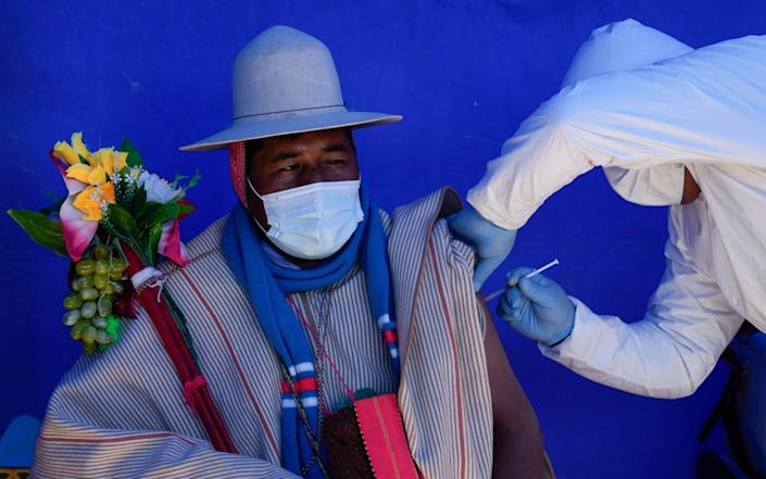 A resident is inoculated with a dose of the Sinopharm Covid-19 vaccine during a vaccination campaign targeting the Uru Chipaya Indigenous community - AP Photo/Juan Karita