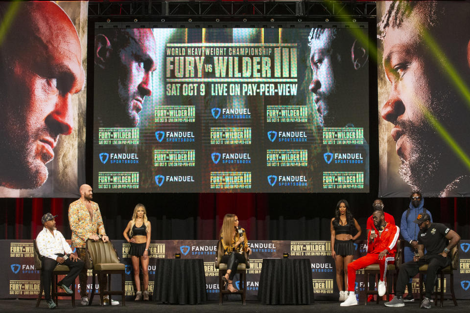 Tyson Fury, standing left, and Deontay Wilder, seated, in red, participate in a news conference in advance of their heavyweight title boxing bout, in Las Vegas on Wednesday, Oct. 6, 2021. (Erik Verduzco/Las Vegas Review-Journal via AP)