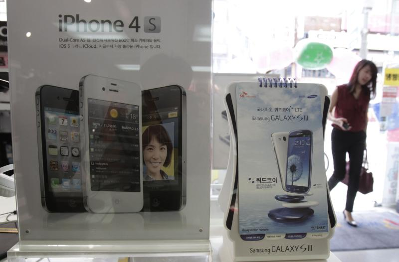 Banners advertising Samsung Electronics' Galaxy S III and Apple's iPhone 4S are displayed at a mobilephone shop in Seoul, South Korea, Monday, Aug. 27, 2012. After more than three weeks of trial in the U.S. and two days of deliberations, the nine-person jury said Friday that Samsung copied Apple's iPhone and iPad and ordered the South Korean firm to pay more than $1 billion in damages. (AP Photo/Ahn Young-joon)