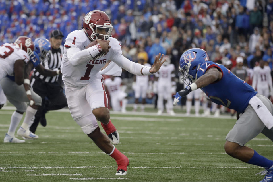 Oklahoma quarterback Jalen Hurts (1) gets past Kansas safety Jeremiah McCullough (12) as he runs the ball during the first half of an NCAA college football game Saturday, Oct. 5, 2019, in Lawrence, Kan. (AP Photo/Charlie Riedel)