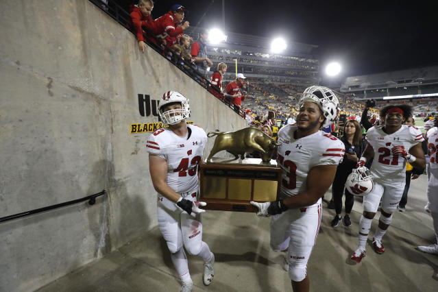 Wisconsin linebackers Ryan Connelly, left, and T.J. Edwards, right, carry the Heartland Trophy off the field after the team's 28-17 win over Iowa in an NCAA college football game, Saturday, Sept. 22, 2018, in Iowa City. (AP Photo/Matthew Putney)