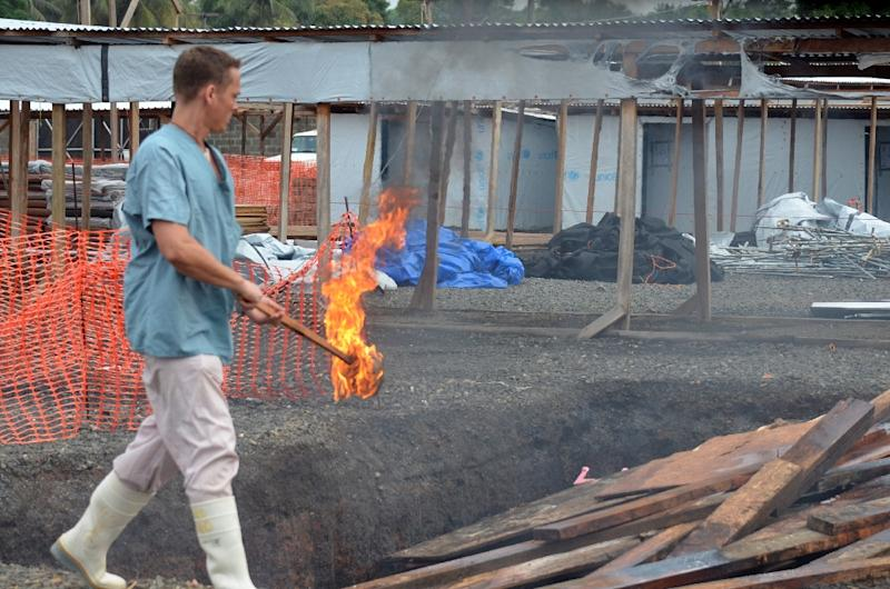 A Medecins Sans Frontieres worker burns pieces of wood on January 27, 2015 as a Ebola treatment centre in Monrovia is decommissioned (AFP Photo/Zoom Dosso)