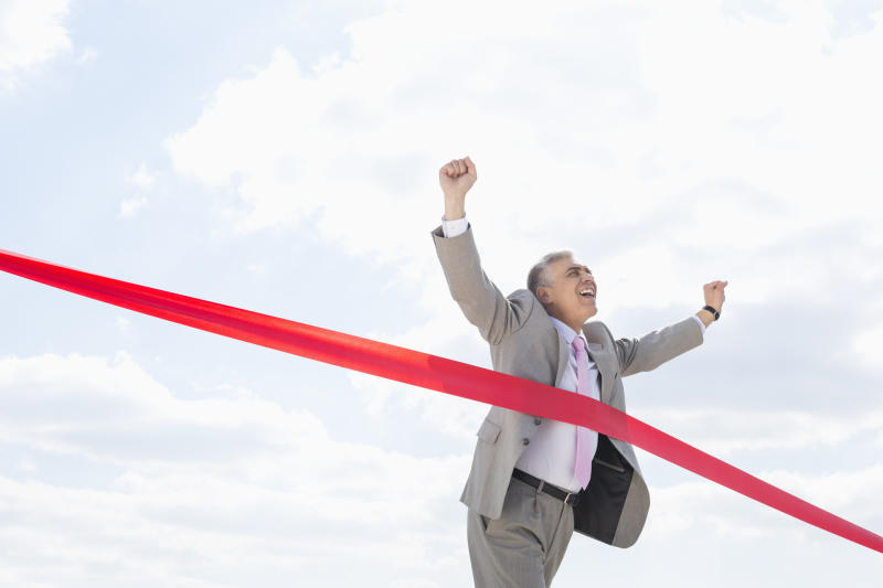 An older man crosses a red tape signifying the finish line to a race and holds his hands up in victory.