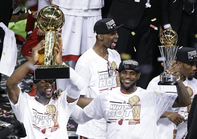 FILE - In this June 21, 2013 file photo, the Miami Heat's Dwyane Wade, left, holds the Larry O'Brien NBA Championship Trophy as LeBron James holds his Bill Russell NBA Finals Most Valuable Player Award after Game 7 of the NBA basketball championship against the San Antonio Spurs, in Miami. The Heat's Chris Bosh celebrates in the background. A person familiar with the situation tells The Associated Press that James has decided to opt out of the final two years of his contract with the Heat and become a free agent on July 1. Opting out does not mean James has decided to leave the Heat, said the person, who spoke on condition of anonymity because neither the four-time NBA MVP nor the team had made any public announcement.(AP Photo/Wilfredo Lee, File)