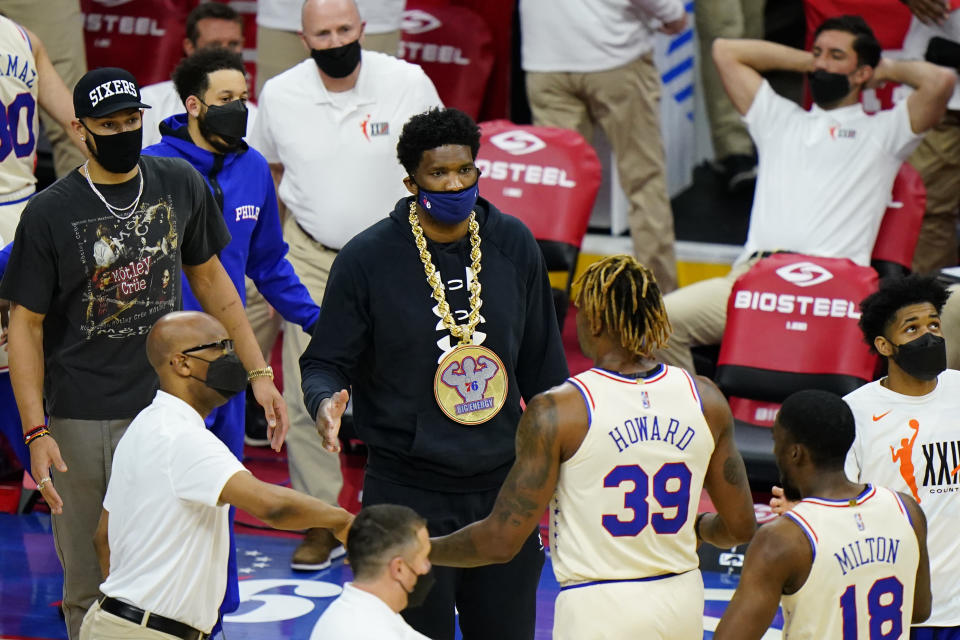 Philadelphia 76ers' Ben Simmons, from left, and Joel Embiid greet Dwight Howard and Shake Milton during a timeout in the first half of an NBA basketball game against the Orlando Magic, Sunday, May 16, 2021, in Philadelphia. (AP Photo/Matt Slocum)