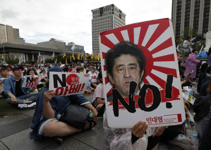 """FILE - In this Aug. 15, 2019, file photo, a protester holds an image of Japanese Prime Minister Shinzo Abe during a rally denouncing Abe and also demanding the South Korean government to abolish the General Security of Military Information Agreement, or GSOMIA, an intelligence-sharing agreement between South Korea and Japan, in downtown Seoul, South Korea. Squeezed between a growing North Korean threat and a shaky alliance with the United States, South Korea must decide this week whether its national pride and deep frustrations with Japan are worth killing a major symbol of their security cooperation with Washington. The letters read """"No Abe."""" (AP Photo/Lee Jin-man, File)"""