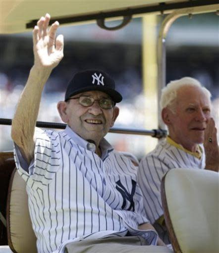 New York Yankees Hall of Famers Yogi Berra, left, and Whitey Ford sit in the shade of a golf cart as they are introduced before the Yankees Old Timers Day baseball game, Sunday, June 23, 2013, at Yankee Stadium in New York. (AP Photo/Kathy Willens)