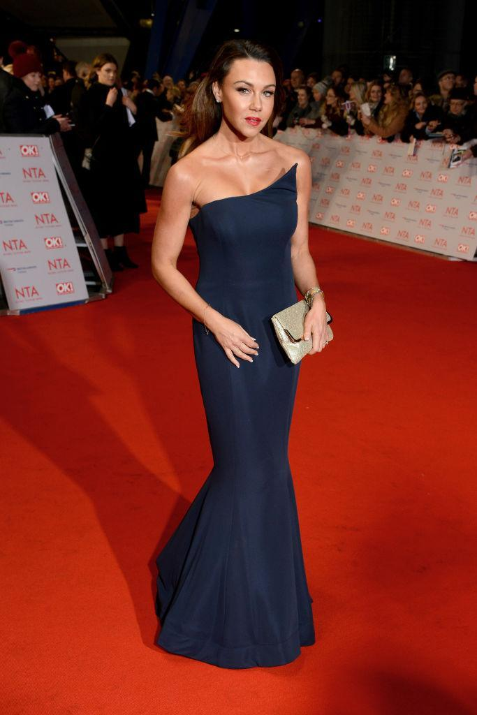 <p>Michelle Heaton opted for a navy blue cold-shoulder dress for the ceremony and finished the look with a bold lip. <em>[Photo: Getty]</em> </p>