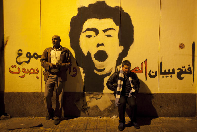 """Two Egyptian protesters takes a souvenir photo by graffiti that reads in Arabic """"open the doors of silence and shout loudly,"""" made by the protesters at the walls of the presidential palace during protests opposing Muslim Brotherhood and Egyptian President Mohammed Mosri, after having broken through a barbed wire barricade keeping them from getting closer to the presidential palace, in Cairo, Egypt, Friday, Dec. 7, 2012. Egypt's political crisis spiraled deeper into bitterness and recrimination Friday as thousands of Islamist backers of the president vowed vengeance at a funeral for men killed in bloody clashes earlier this week and large crowds of the president's opponents marched on his palace to increase pressure after he rejected their demands. (AP Photo/Nasser Nasser)"""