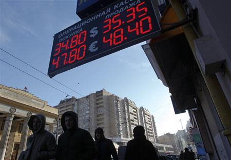 People walk past a currency exchange showing rouble exchange rates in Moscow