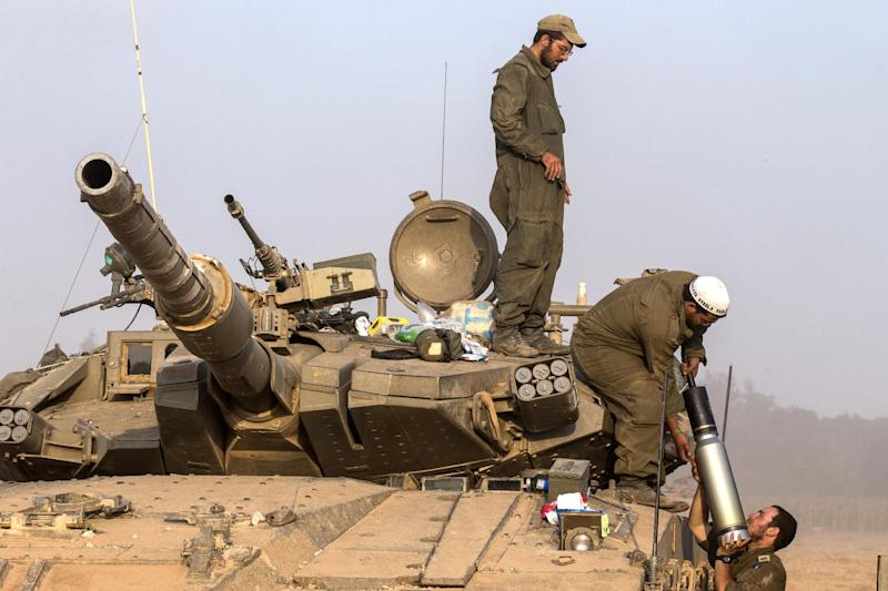 Israeli soldiers carry a shell as they prepare their Merkava tanks stationed along the Israeli Gaza border, on July 22, 2014
