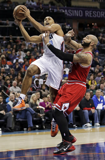 Charlotte Bobcats' Gerald Henderson, left, drives past Chicago Bulls' Carlos Boozer, right, during the first half of an NBA basketball game in Charlotte, N.C., Saturday, Jan. 25, 2014. (AP Photo/Chuck Burton)