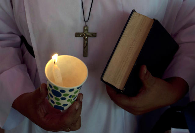 <p>A Pakistani Christian holds candle during a vigil to pay tribute to the victims of Wednesday's bus attack, in Karachi, Pakistan, May 15, 2015. (AP Photo/Shakil Adil) </p>