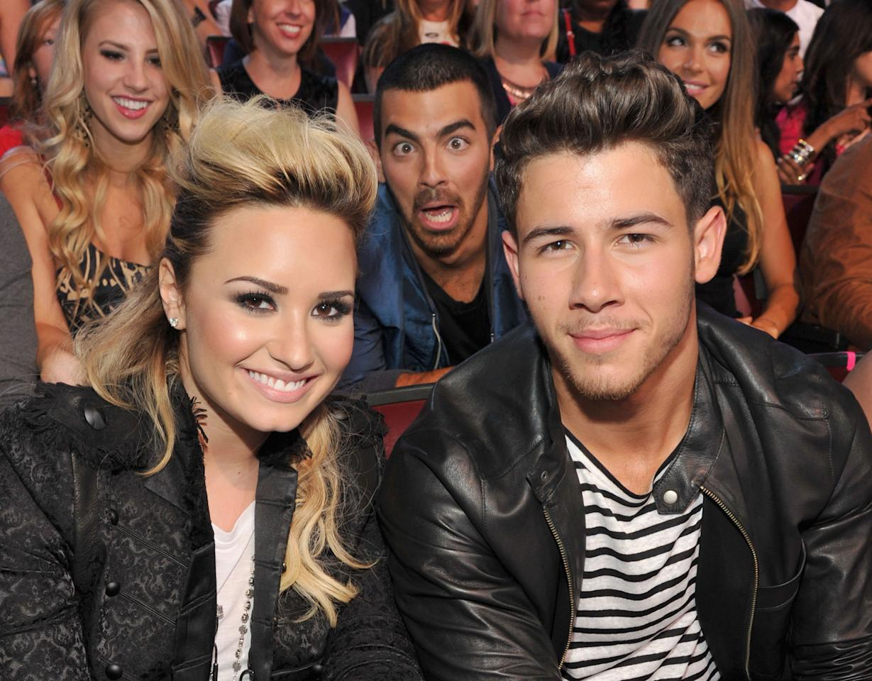 Did somebody say Jonas? Big bro Joe snuck into Nick's shot with Demi Lovato at the Teen Choice Awards. (8/11/13) Credit: Kevin Mazur/WireImage