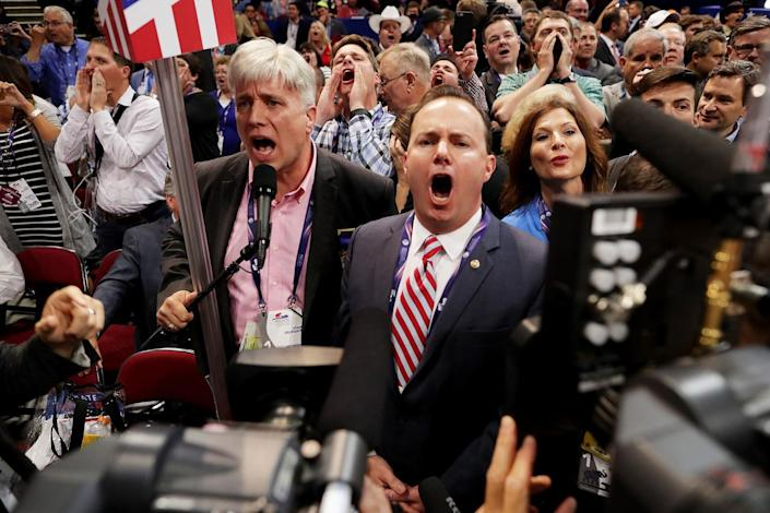 <p>Sen. Mike Lee, (R-UT) © and Phil Wright, Vice Chair of the Utah State Delegation (L) shout no to the adoption of rules without a roll call vote on the first day of the Republican National Convention on July 18, 2016 at the Quicken Loans Arena in Cleveland, Ohio. (Chip Somodevilla/Getty Images)</p>