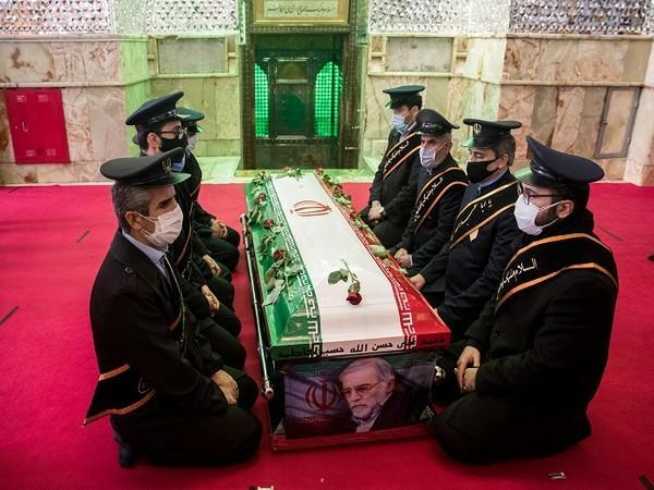 Mourners sit next to the coffin of Iranian nuclear scientist Mohsen Fakhrizadeh during the burial ceremony at the shrine of Imamzadeh Saleh, in Tehran, Iran. (Photo Credit: Reuters)