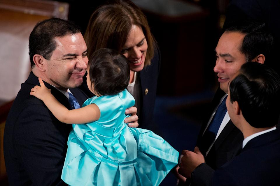 Rep. Henry Cuellar (D-Texas) holds Andrea Elena Castro, daughter of Joaquin Castro (D-Texas), second from right, before the 114th Congress was sworn in on the House floor of the Capitol on Jan. 6, 2015.