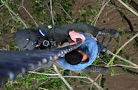 A man who got trapped in a flood and was clinging to a tree is rescued by members of the Honduran Air Force in Choloma, Honduras