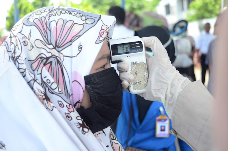 Port health workers check the body temperature of passengers from Malaysia who arrive at Nusantara Port, Parepare City. Source: Getty Images