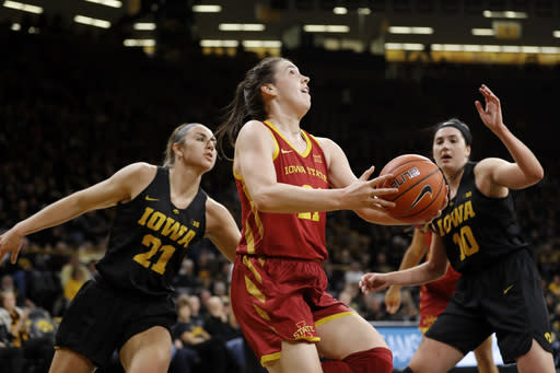 Iowa State guard Bridget Carleton, center, drives to the basket between Iowa's Hannah Stewart, left, and Megan Gustafson, right, during the first half of an NCAA college basketball game, Wednesday, Dec. 5, 2018, in Iowa City, Iowa. (AP Photo/Charlie Neibergall)