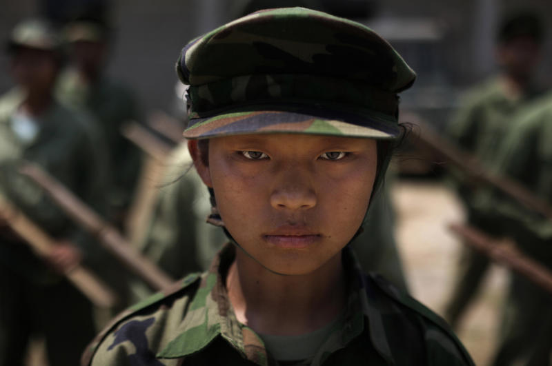 FILE - In this April 17, 2010 file photo, a young female recruit of the Kachin Independence Army, one of the country's largest armed ethnic groups, participates in battle drills at a training camp near Laiza in Myanmar. As military-ruled Myanmar prepares for its first election in two decades, some of its powerful ethnic minorities, fearing a hopeless post-election future, are preparing for war. (AP Photo/Ng Han Guan, File)
