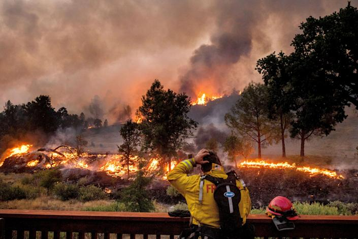 A firefighter watches the LNU Lightning Complex Fire spread through the Berryessa Estates neighborhood of unincorporated Napa County, Calif., on Aug. 21. The blaze forced thousands to flee and destroyed hundreds of homes and other structures.