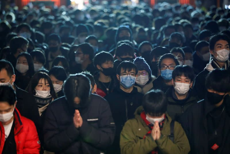 People wearing protective face masks offer prayers on the first day of the New Year at the Kanda Myojin shrine, amid the coronavirus disease (COVID-19) outbreak in Tokyo
