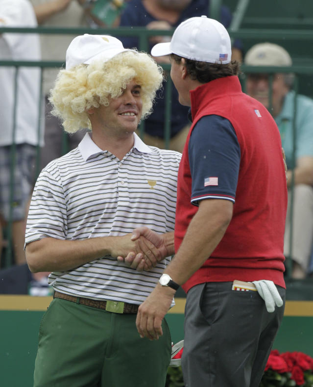 International team player Louis Oosthuizen, left, of South Africa, wears a wig onto the first tee as he greets United States team player Phil Mickelson before the start of the four-ball match at the Presidents Cup golf tournament at Muirfield Village Golf Club Thursday, Oct. 3, 2013, in Dublin, Ohio. (AP Photo/Jay LaPrete)