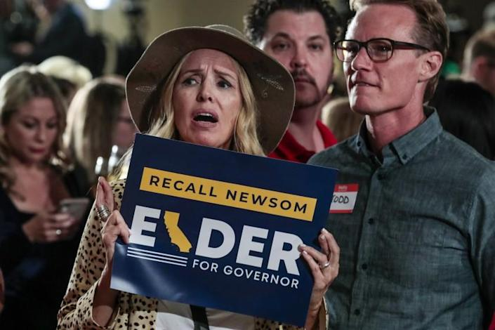 Costa Mesa, CA, Tuesday, September 14, 2021 - Kellie Avakian crosses her fingers but shows disappointment as poll results are broadcast showing a nearly 70 percent vote against the recall of Governor Newsom at a rally for candidate Larry Elder at the Orange County Hilton. (Robert Gauthier/Los Angeles Times)