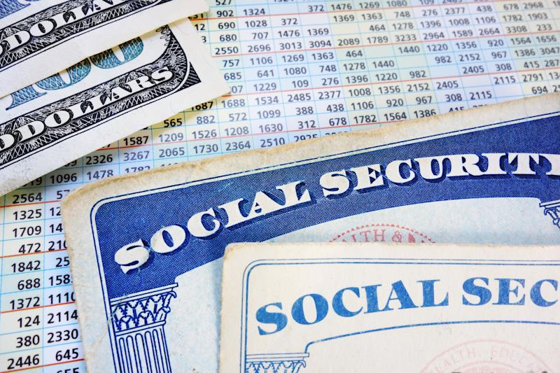 Two Social Security cards, and two hundred dollar bills, lying atop a Social Security payout card.