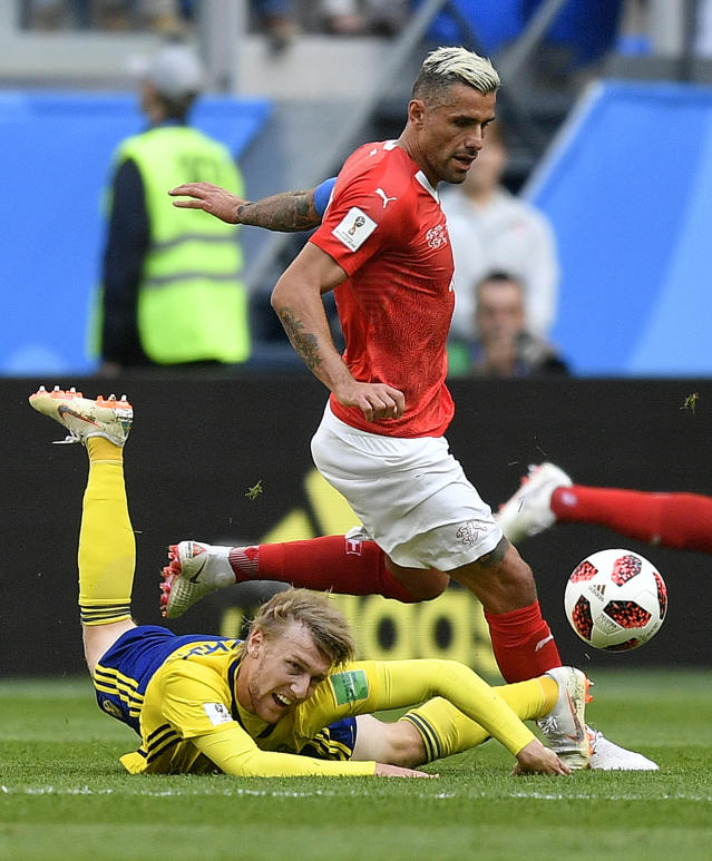 <p>Switzerland's Valon Behrami, rear, and Sweden's Emil Forsberg challenge for the ball during the round of 16 match between Switzerland and Sweden at the 2018 soccer World Cup in the St. Petersburg Stadium, in St. Petersburg, Russia, Tuesday, July 3, 2018. (AP Photo/Martin Meissner) </p>