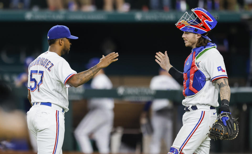 Texas Rangers relief pitcher Joely Rodriguez (57) and catcher Jonah Heim celebrate a 5-3 win over the Oakland Athletics after a baseball game, Wednesday, June 23, 2021, in Arlington, Texas. (AP Photo/Brandon Wade)