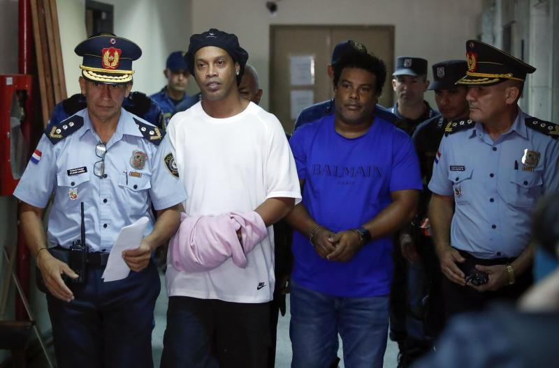 Former soccer star Ronaldinho, second from left, and his brother Roberto de Assis Moreira walks escorted by police officers to declare to judge Clara Ruiz Diaz at Justice Palace in Asuncion, Paraguay, Saturday, March 7, 2020. Ronaldinho and his brother Roberto were alleged to enter to the country with a false Paraguayan passport.(AP Photo/Jorge Saenz)
