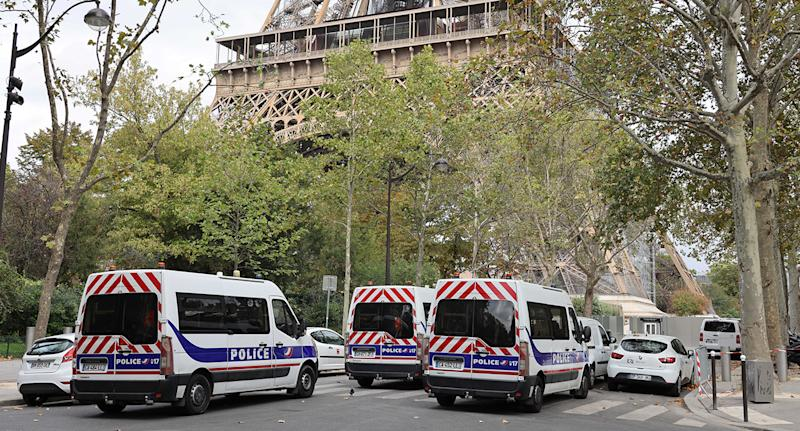 Three police vans are pictured in a street below the Eiffel Tower in Paris.