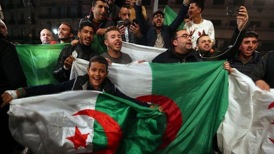 People wave Algeria's national flags in Algiers. Photo: 2 April 2019