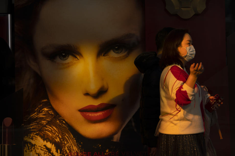 A woman wearing a face mask to protect against the spread of the coronavirus walks past a billboard at an outdoor shopping area in Beijing, Saturday, Feb. 20, 2021. China has been regularly reporting no locally transmitted cases of COVID-19 as it works to maintain control of the pandemic within its borders. (AP Photo/Mark Schiefelbein)