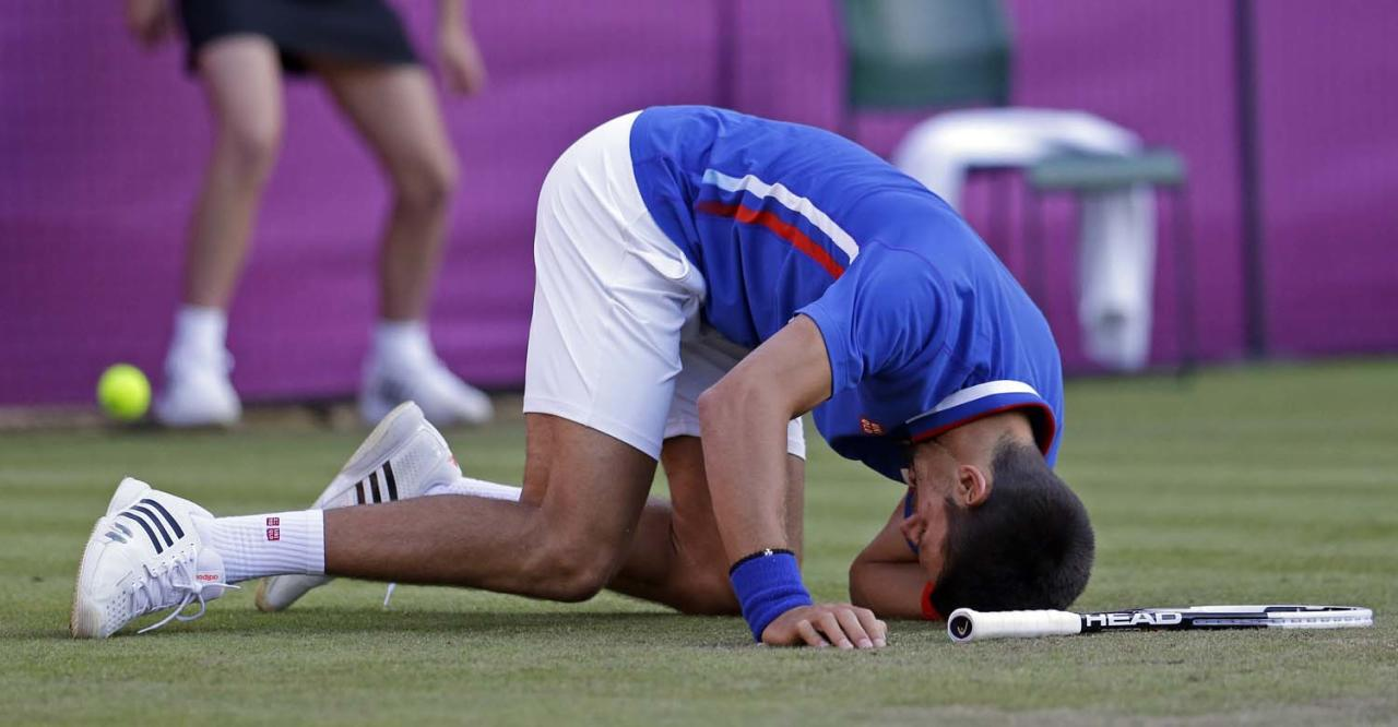 Novak Djokovic of Serbia slips on the grass as he plays Fabio Fognini at the All England Lawn Tennis Club at Wimbledon, in London, at the 2012 Summer Olympics, Sunday, July 29, 2012. The match was interrupted for several hours by rain. (AP Photo/Mark Humphrey)