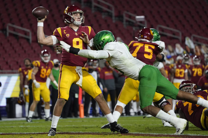 Southern California quarterback Kedon Slovis (9) is tackled by Oregon defensive end Kayvon Thibodeaux (5) during the second quarter of an NCAA college football game for the Pac-12 Conference championship Friday, Dec 18, 2020, in Los Angeles. (AP Photo/Ashley Landis)