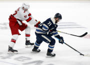 Columbus Blue Jackets forward Nick Foligno, right, controls the puck against Carolina Hurricanes defenseman Brett Pesce during the second period of an NHL hockey game in Columbus, Ohio, Sunday, Feb. 7, 2021. (AP Photo/Paul Vernon)