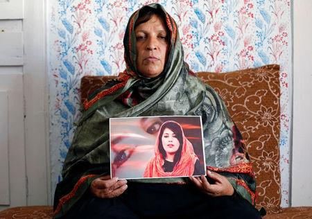 Anisa Mangal holds a photo of her daughter Mena Mangal in Kabul